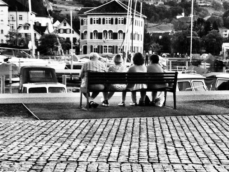 Some people sitting by a lake...in Switzerland