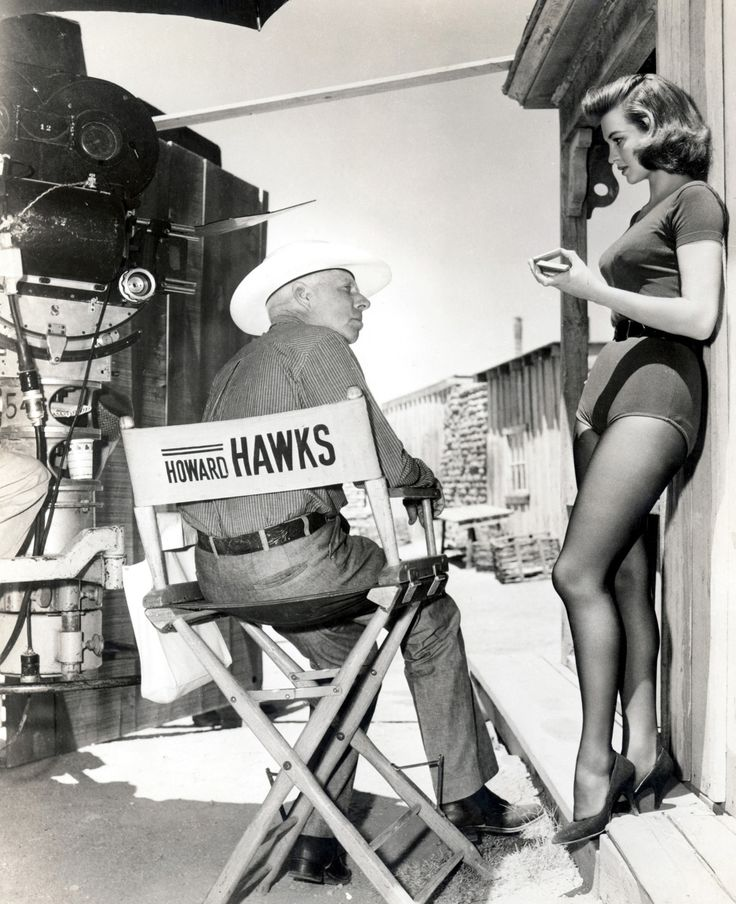 "Director Howard Hawks talks with gorgeous Angie Dickinson on the set of ""Rio Bravo""."