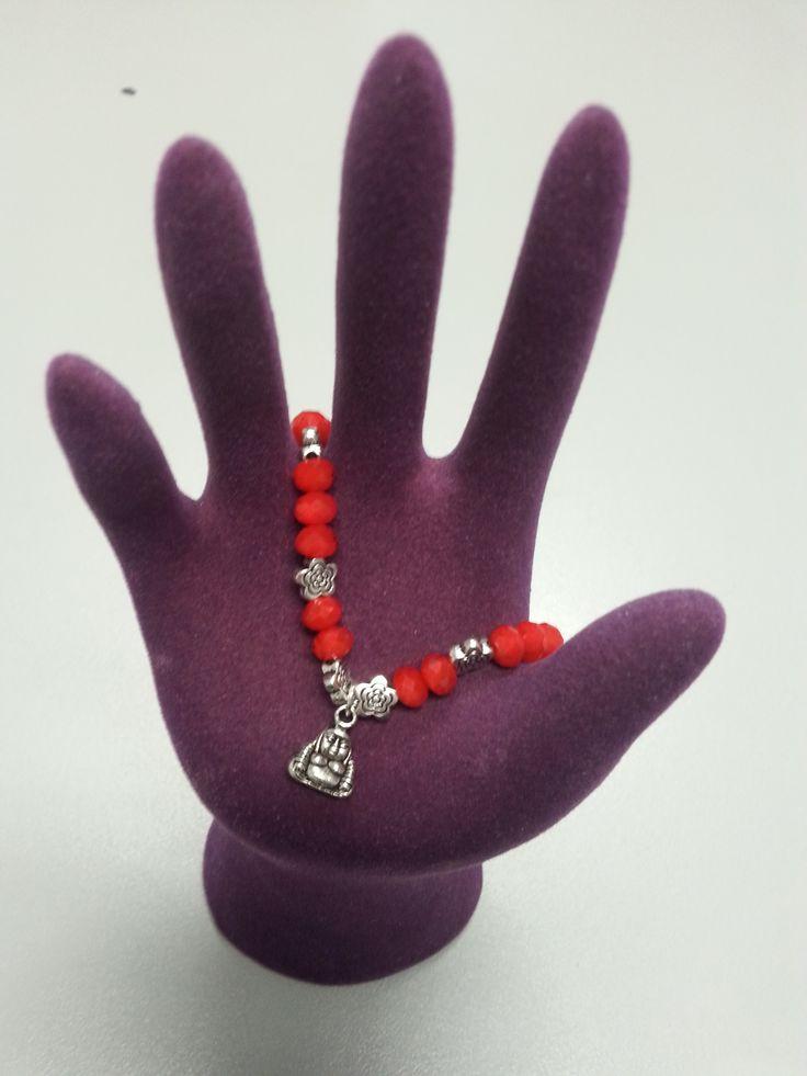 Pulsera de piedras rojas con pequeños remaches de plata en forma de flor y un buda. Perfecta para cualquier ocasión.