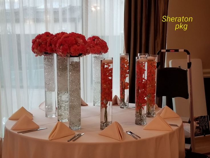 Tall cylinder vase with a topper of hot pink hydrangea and carnations. Along with submerged orchids.