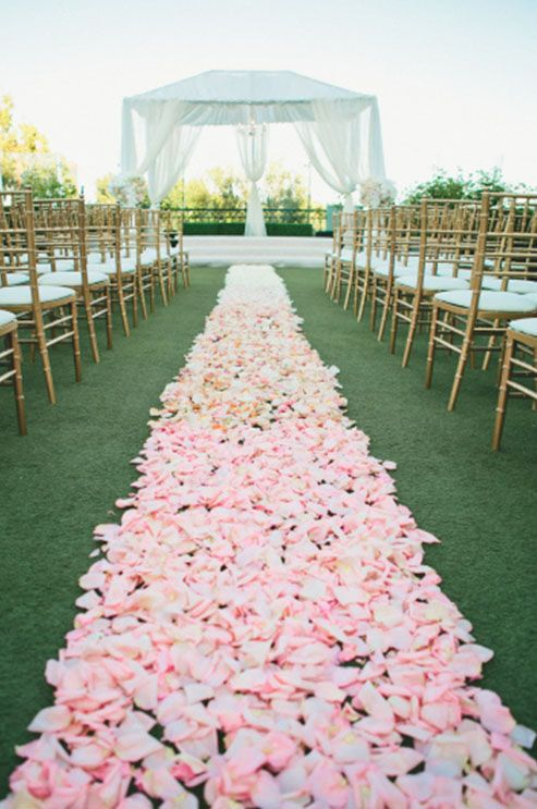 10 Breathtaking Ideas For Planning A Summer Wedding: For a garden wedding, create a serpentine aisle of flower petals leading to the altar. Vibrant pinks and oranges lend themselves oh-so-nicely to summer color schemes. Photo by OneLove Photography