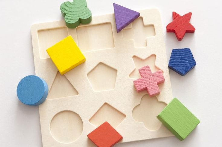 Close up of various shaped scattered puzzle block pieces scattered over template on gray background - free stock photo from www.freeimages.co.uk