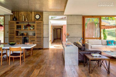 Madeira de demolição (Madeireira Vale), protegida por cera incolor, reveste todo o piso. No centro da foto, vê-se o corredor que liga o módulo social ao íntimo. Projeto de Skylab Arquitetos.