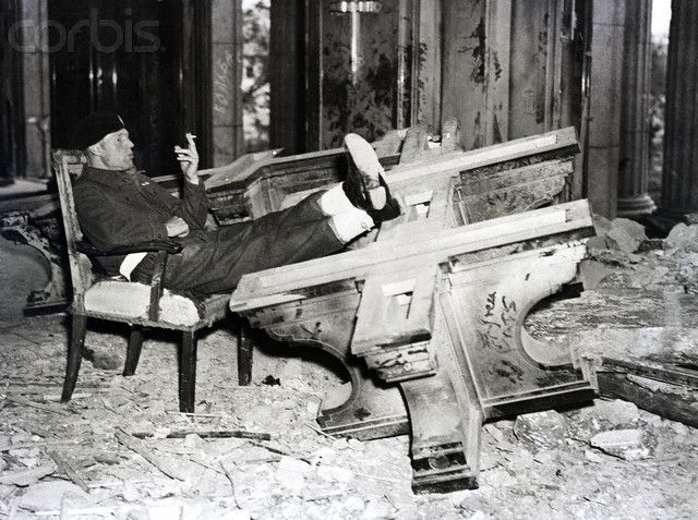 Trooper Seated In Adolph Hitler'S Chair - BE035137 - Rights Managed - Stock Photo - Corbis. Original caption:8/17/45-Berlin, Germany: Having a free day, trooper Edward Law, stationed in Berlin, took a tour of the German capital. He chanced upon the ruins of the chancellery which he entered. Here he is seen as he seated himself in the chair lated vacated by Adolph Hitler. His foot rest is the table Hitler used when he plotted world conquest.