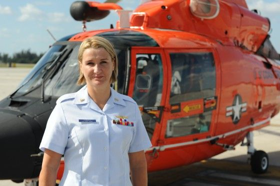Chief Petty Officer Karen Voorhees stands in front of an MH-65 Dolphin rescue helicopter, a common platform for her search and rescue missions.  Voorhees is the first woman to be advanced to chief petty officer in the rate of aviation survival technician since women were integrated into Coast Guard active duty service in 1973.  U.S. Coast Guard photo by Petty Officer 3rd Class Jon-Paul Rios.