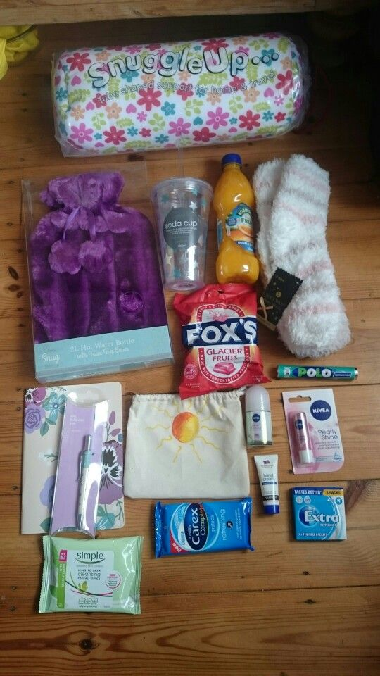 Hospital care package: hot water bottle, plastic cup with straw, squash, cushion, slipper socks, hard boiled sweets, mints, chewing gum, notebook& pen, small toiletries and wipes