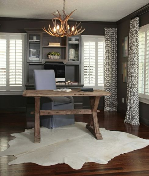Black walls and antler chandelier in an office with patterned drapes and Plantation shutters