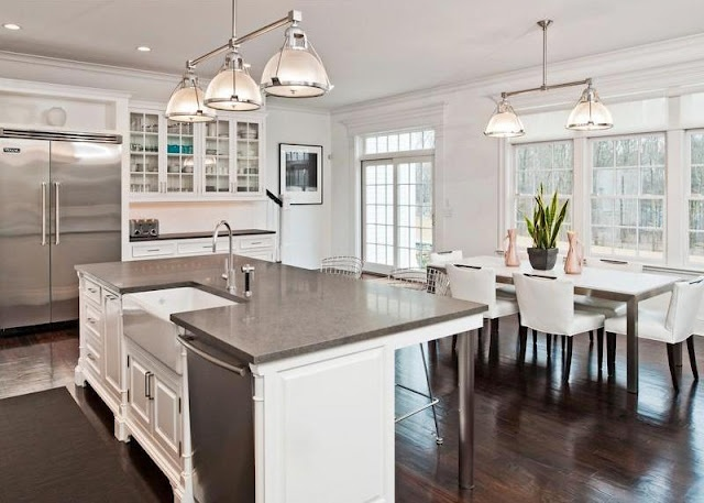 The white kitchen with gray counters and stainless appliances leans is more of a nod to the traditional bones of the home