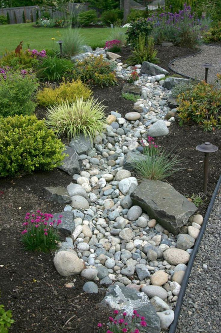 create a beautiful and low maintenance garden incorporating river rock landscaping with a dry stream