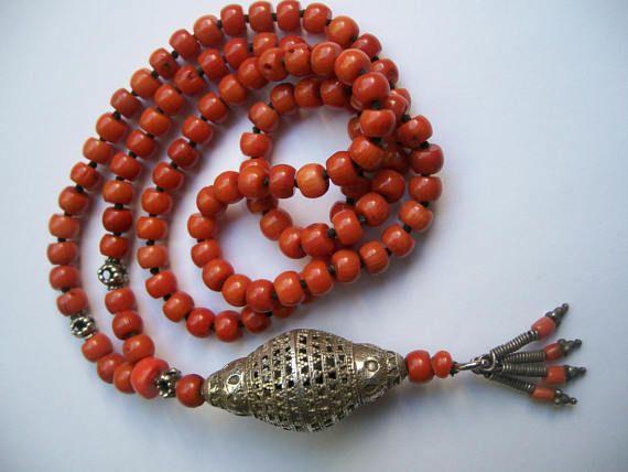 Mala (Boeddhistische meditatieketting). Deze mala heb ik handgeknoopt. Ik gebruikte 108 kralen bamboe koraal. De kralen van de mala worden van elkaar gescheiden deur een knoopje. Deze mala is handgeknoopt op zwart waskoord. Grote antieke zilveren filigrain kraal uit Jemen. Deze antieke kraal is uitzonderlijk mooi en zeldzaam, prachtig handwerk met kleine korrels (bolletjes). Kleinere zilveren kralen zijn sterling zilveren kralen uit Bali. Uiteinde mala is gemaakt van onderdelen van een…