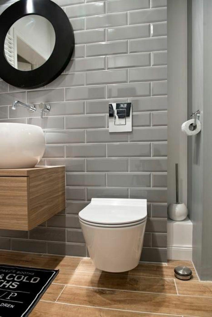 amenagement salle de bain, carrelage mural en gris pastel, meuble wc blanc suspendu, meuble lavabo suspendu, lavabo rond, miroir rond au cadre noir, tapis noir avec des inscriptions amusantes en blanc