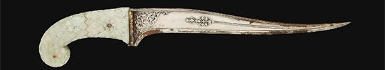 Found in Elysium. The blade if the typical double-curved shape featured by these daggers, the forte having carved floral decoration, while the gold-damascened flat spine is carved with six deep grooves. The hilt is decorated with floral lattice overall with three red gem insets, with possibly original green velvet covered sheath with carved agate finials.