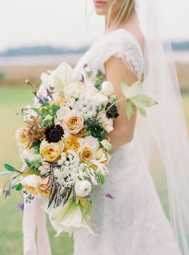 Winter bouquet with golden mustard roses, ranunculus, queen anne's lace, clematis, and pieris japonica buds by Lanson B. Jones & Co. Floral & Events
