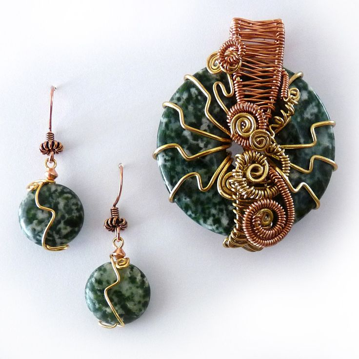 Ornate and bold. A dark green tree agate donut is wrapped abstractly in copper and bronze. The copper bail is hand woven and bold coils and rays form an alluring sculpture. This is a very solid piece