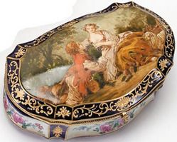 Year: 1901 - 1930 A Sevres style porcelain bijouterie box, early 20th century, The shaped hinged lid decorated with a romantic scene of lovers, against a cobalt blue ground enriched with gilt.