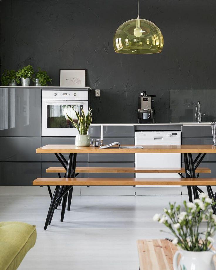 Retkihenkinen pitkä puupöytä ja keltainen Kartell FL/Y valaisin tuovat hauskan kontrastin keittiön harmaaseen tyyliin.