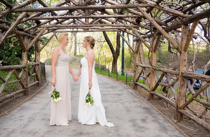 brides under a rustic archway by the lake in Central Park