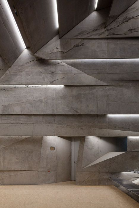 Bavarian concert hall featuring a rough stone exterior and a raw concrete interior.