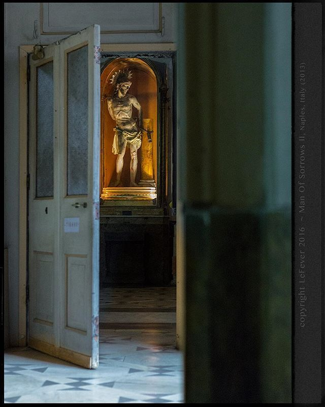 'Man of Sorrows' From inside, outside, to inside Maria della Grazie a Toledo, Naples, Italy, a glimpse at her 'Man of Sorrows' through an open doorway.  #church #catholic #catholicchurch #christian #christ #statue #manofsorrows #lighting  #jesus #lefeverconsecrated #picoftheday #photoftheday #jefflefever #jefflefeverphotography #italy #italia #door #doors #doorway