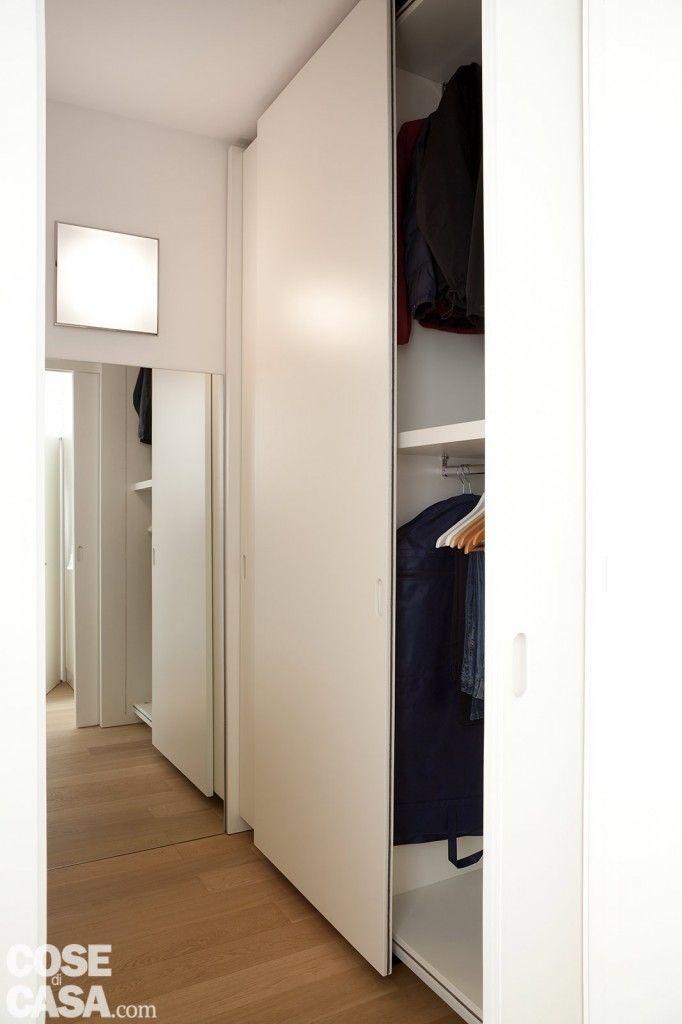 Il vano #guardaroba è attrezzato con due armadi a tutt'altezza posti di fronte e dotati di ante scorrevoli salvaspazio. Sono realizzati su misura in laccato bianco opaco. Sulla parete di fondo, lo specchio applicato direttamente al muro e un'applique per illuminare.