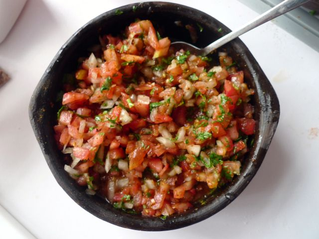 """The base recipe of the salsa is known as Pebre, which is a Chilean condiment made of cilantro, chopped onion, olive oil, garlic and chile peppers.  Pebre is a sauce that is typically added to soups and stews, or it can used in the same fashion as ketchup.  Adding fresh chopped tomatoes turns Pebre into Chilean Salsa, or Chancho en Piedra (""""Pig on a Rock"""")...."""