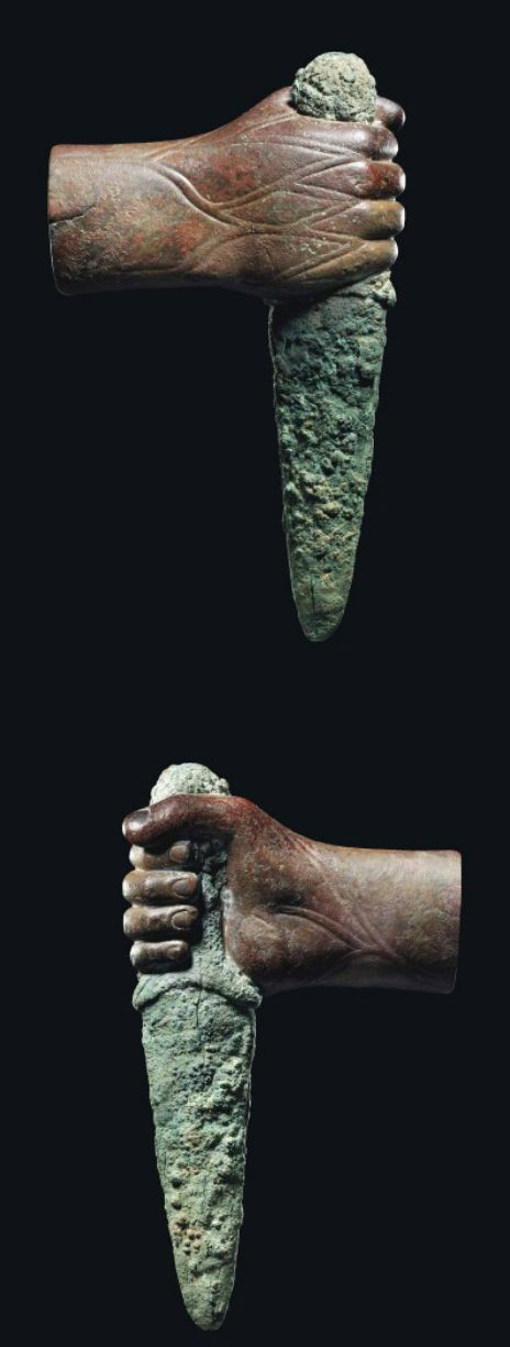 A WESTERN ASIATIC COPPER HAND WITH DAGGER CIRCA MID-LATE 3RD MILLENNIUM B.C. The right hand clenching the hilt of a short bronze dagger with a triangular blade, with stylized veining on the back of the hand and wrist and remains of silver fingernails