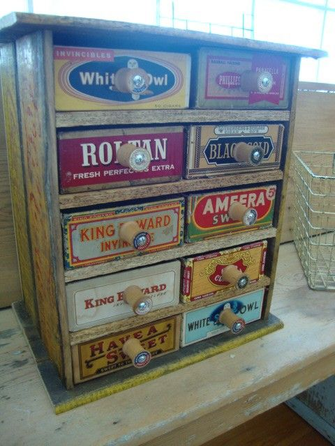 """Cabinet made from a coca-cola crate, cigar boxes & thread spools as """"drawer"""" pulls."""