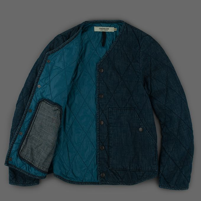 Omnigod Denim Quilted Jacket in Indigo Angle - Made in Japan   A soft denim quilted jacket that is fully lined and snaps down the front. Very lightly padded to keep the chill out   - 100% cotton with a light thinsulate polyester and 100% Nylon lining - Binded edges  - Front welt pockets with stitch through detail  - Interior twill loop at back neck