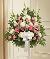 Send a sympathy floral standing spray created by a local florist for hand delivery. Seasonal flowers are arranged in this beautiful gift to show your care and concern. With pastel roses, lilies, mums, snapdragons and more. Standing sprays are an appropriate gift for delivery from a family member, friend or co-worker. Delivery is available directly to a funeral home from our local florist partners. Order today before 3pm in the delivery zip code for same day delivery. Medium (shown) measures…