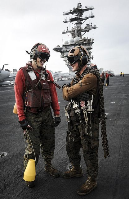 "GULF OF OMAN (July 15, 2013) - Cpl. Mathew Giles, left, a native of King George, Va., and Lance Cpl. Joseph Daugherty, a native of Independence, Mo., assigned to the ""Death Rattlers"" of Marine Fighter Attack Squadron (VMFA) 323, stand on the flight deck of the aircraft carrier USS Nimitz (CVN 68)"