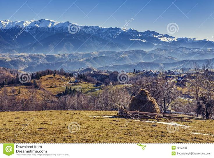 Alpine rural scenery with sheepcote, haystack and remote village in the valleys of Bucegi mountains, Brasov county, Romania.