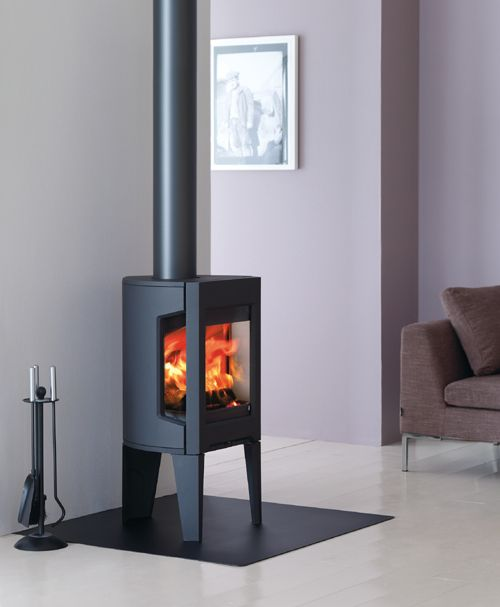 A small, modern stove: F 163 by Jotul. The size and shape allow it to be placed in a corner or flat on a wall even in limited space. Designed with a special glass (that won't accumulate soot!) on the front and sides, the flames of the fire can be enjoyed from all angles.