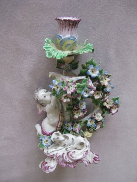 """A fine Bow  candlestick figure of a putto reaching for a bird amongst flowers and foliage. He has a dog at his feet and standing on a rococco shaped base. Impressed T mark  Circa  1765 Height 9"""""""