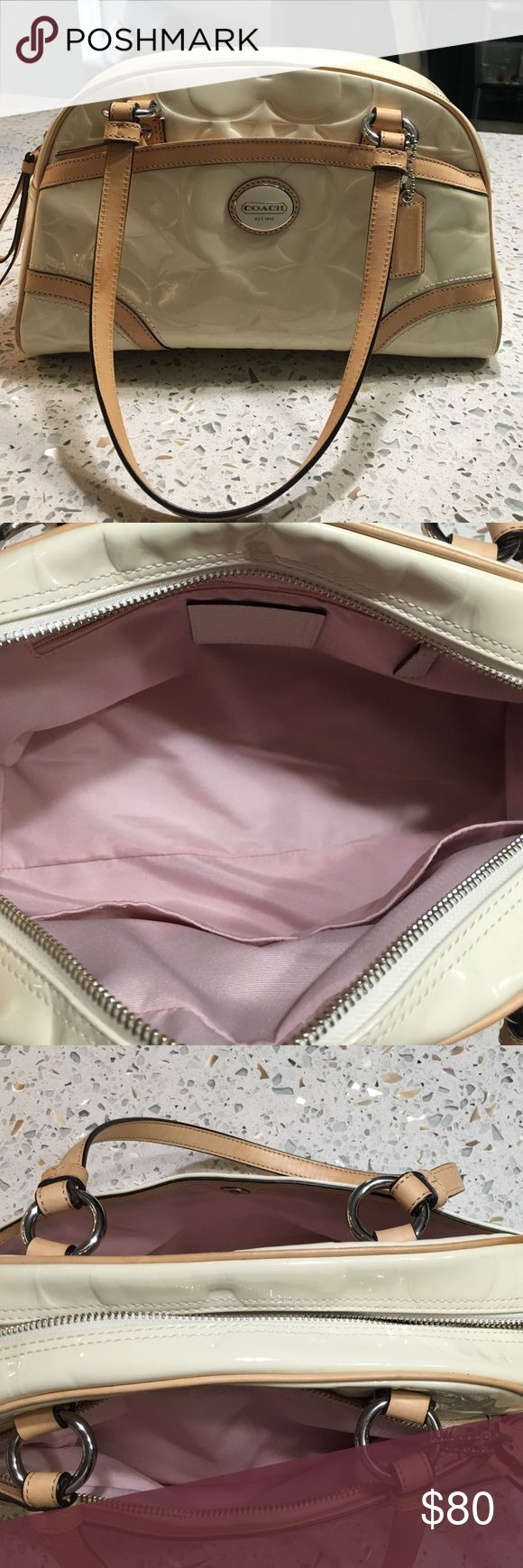 Like NEW Coach handbag Only used two times. Been stored in smoke free home and in a dust bag. Shiny off white with tan leather trim and straps. There are a couple of marks on it that came that way from the store resulting in a slight discount. At the store they said a little fingernail polish may remove it but I was too scared to try. Inside pink fabric lining is clean like new. This is a super cute bag. Please see additional pics on additional post.  Does come with over the shoulder strap…