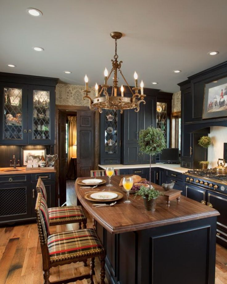 Black distressed cabinets, a few lightened with custom leaded glass panels, provide a gorgeous backdrop for this traditional kitchen. An island with a warm wood countertop is paired with upholstered barstools, providing a cozy dining spot for three.