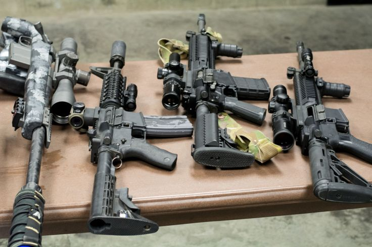 Colt AR-15 rifles and a Spartan Precision .300 Win Mag sniper rifle.