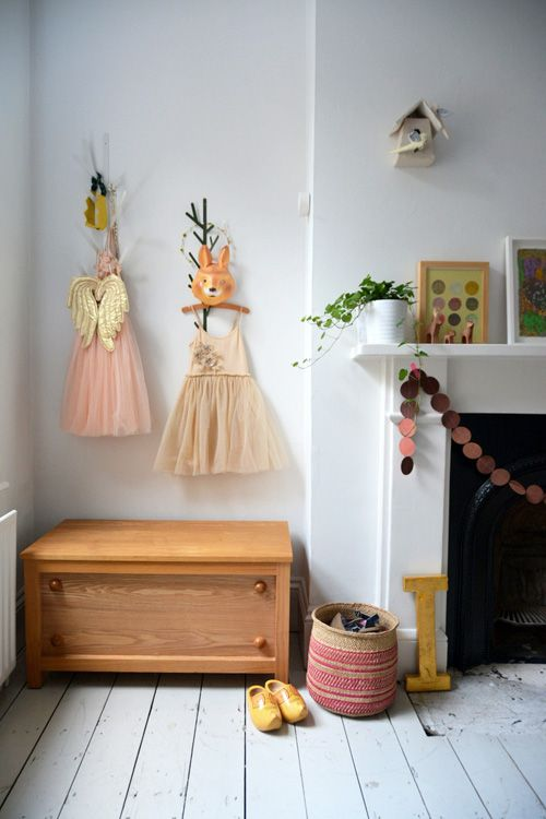 prettiest dresses hung on the wall instead of the closet in a little girl's room