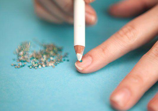 mujer colocandose piedras en las uñas con la ayuda de un lápiz para ojos