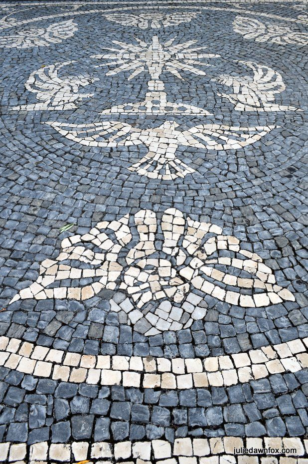 Birds, shells and angels. Religious motifs in cobbled paving outside parish church in Velas, São Jorge island, Azores