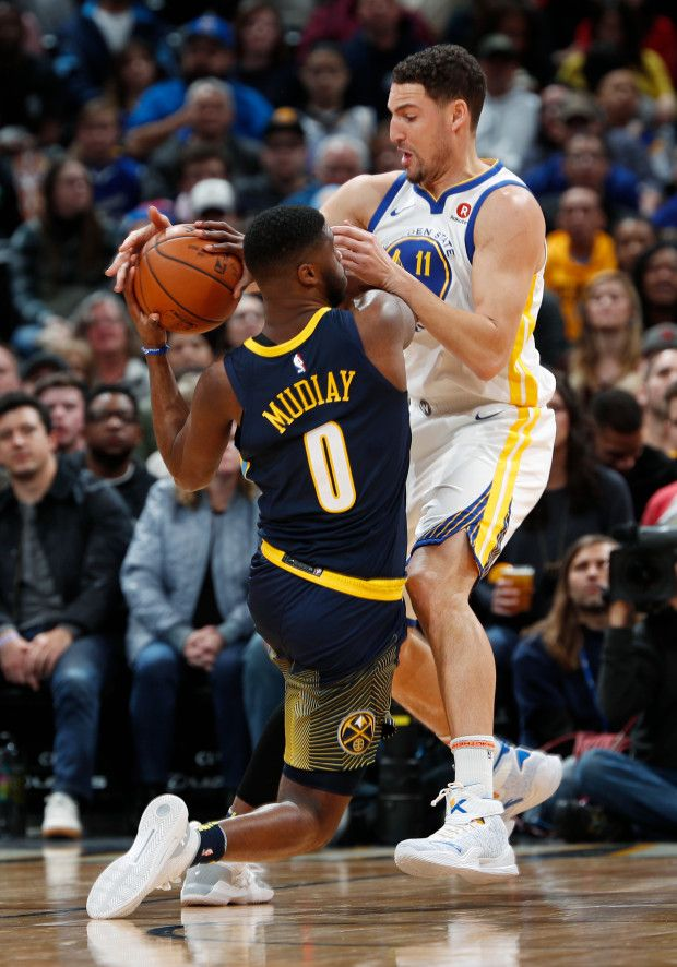 Denver Nuggets guard Emmanuel Mudiay, left, is stopped by Golden State Warriors guard Klay Thompson as he drives to the basket in the first half of an NBA basketball game Saturday, Feb. 3, 2018, in Denver. (AP Photo/David Zalubowski)