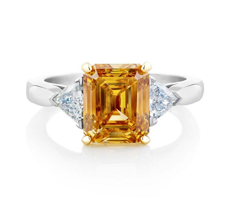 De Beers simple shank emerald-cut Fancy Vivid yellow orange diamond engagement ring in platinum.
