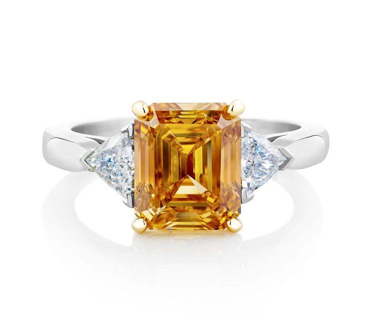 De Beers simple shank emerald-cut Fancy Vivid yellow orange diamond engagement ring in platinum.