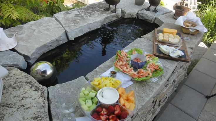 Koi pond from galvanized water trough and stone surround for Pond surround ideas