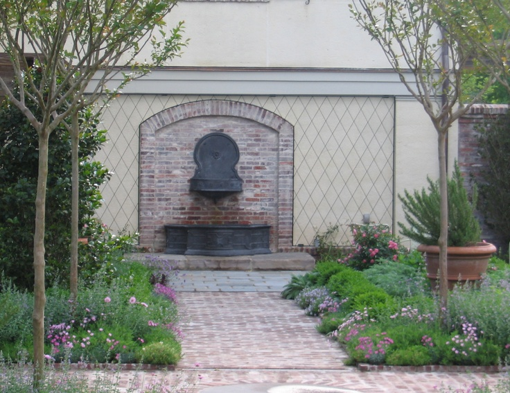 a lead wall fountain and cistern bring the cooling sound of water to a walled garden.