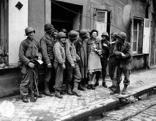 """Cherbourg: Malgrè la barrière de la langue, un groupe d'américains de la 79th ID échangent quelques mots avec la """"Mademoiselle from Normandy"""" sur le seuil d'une maison. Photo prise le 27 juin 1944. La légende américaine de la photo précise que la famille de la jeune femme a été tuée par les Allemands."""