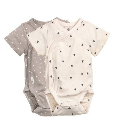 CONSCIOUS. Short-sleeved wrapover bodysuits in soft jersey made from an organic cotton blend. Snap fasteners at side and at gusset.