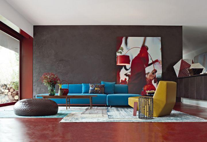 Nel salone a piano terra, dedicato alla socialità e agli incontri di lavoro, esuberanza di colori e una scelta di pezzi Moroso dettata dall'emozione. Lampada di Foscarini, pavimenti in resina rosso terra, su progetto, di Kerakoll