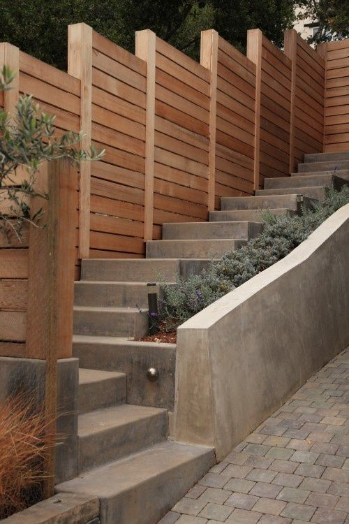 Do you have a steep front or back yard? This is a beautiful and functional way to get around that. | A fence, steps, retaining wall, and raised bed - what more could you ask for?