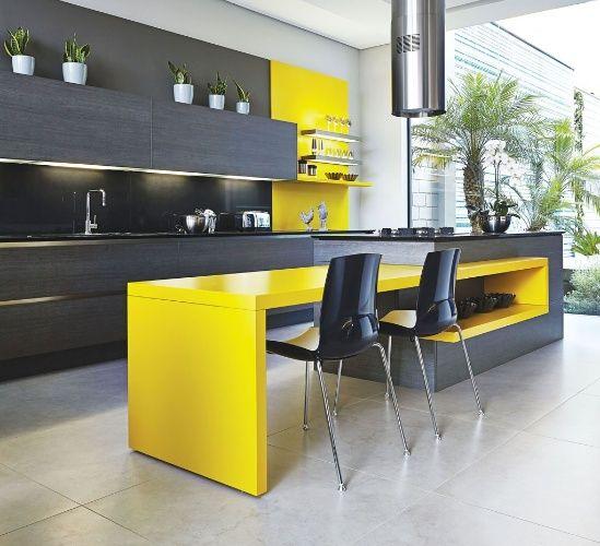Com 20 m² e linhas limpas, a cozinha criada por Ana Maria San Martin combina a sobriedade da madeira escura com o calor e a energia do amarelo. Os armários da Florense são revestidos por lâminas de madeira natural, enquanto a bancada e o painel próximo ao cooktop receberam acabamento em pintura alto brilho