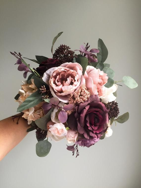 This silk wedding bouquet with its purple, plum and dusty rose tones would add the perfect touch to any fall wedding. This handmade bouquet is made with plum roses, purple skimmia, lavender and purple ranunculus, beige hydrangea, cream magnolias, dusty rose cabbage roses, champagne and